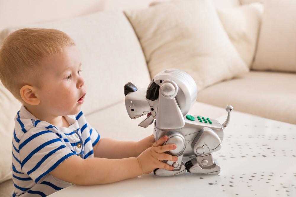 Chłopiec bawi się pieskiem-robotem