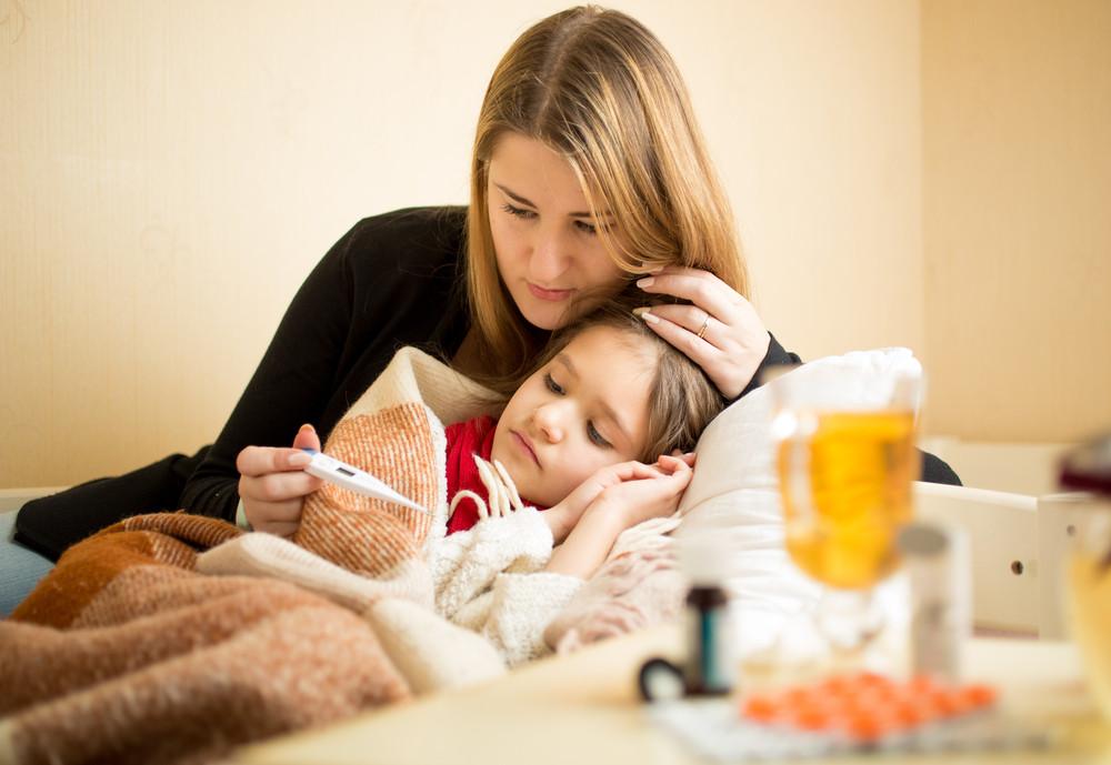 Mama mierzy temperaturę chorej dziewczynce