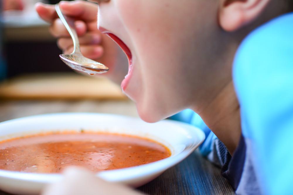 Chłopiec je zupę pomidorową