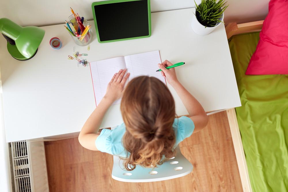 Dziewczynka uczy się przy biurku