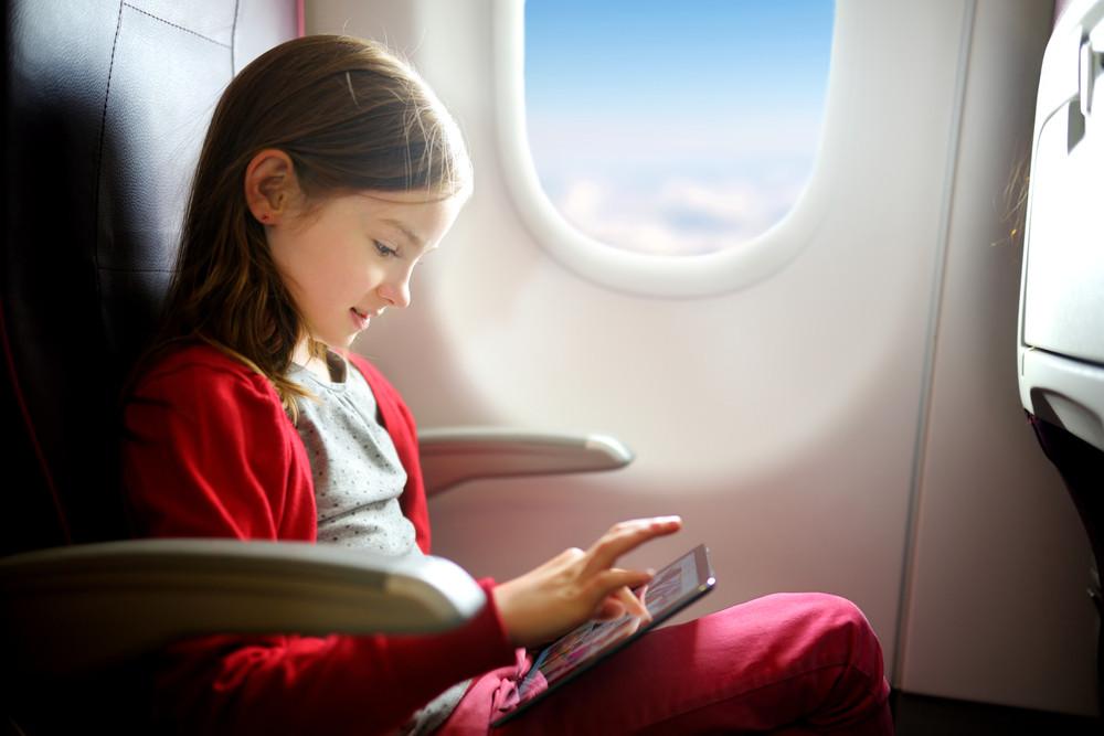 Dziewczynka w samolocie korzystająca z tableta
