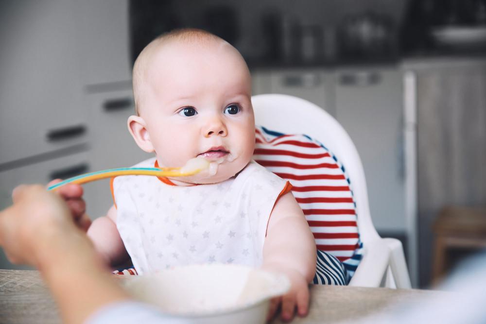 Rodzic karmi dziecko łyżeczką