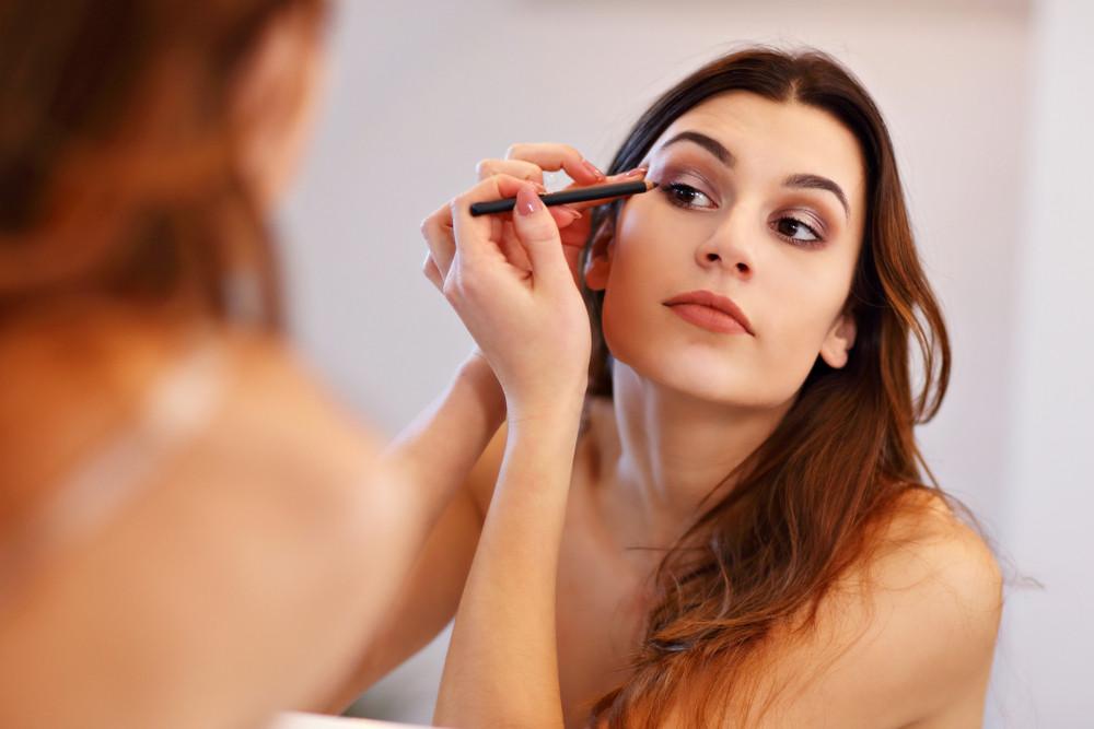 Kobieta wykonuje makijaż oka