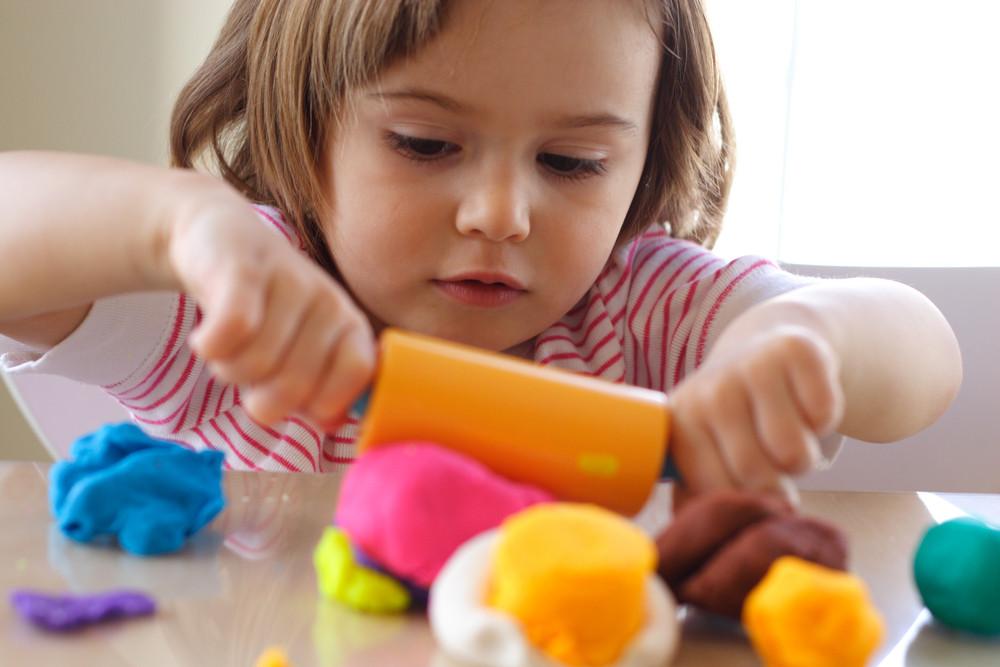 Dziewczynka tworzy zabawki z ciastoliny
