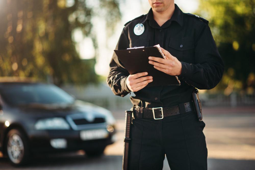 Mężczyzna sporząda raport z kontroli drogowej