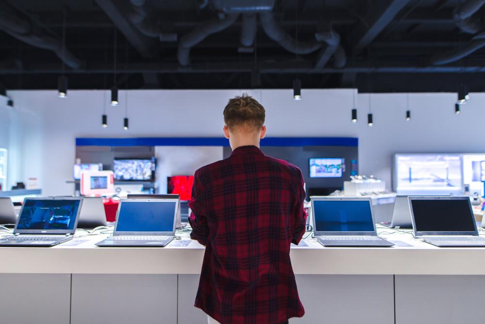 Mężczyzna w sklepie wybiera laptopa