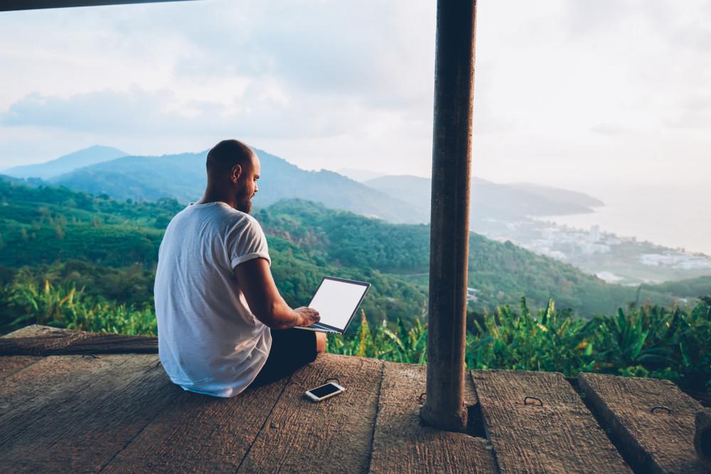 Meżczyzna z laptopem na tle krajobrazu