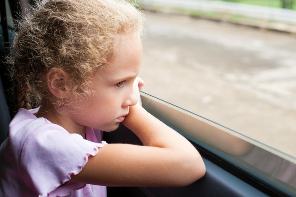 Smutna dziewczynka w samochodzie wygląda przez okno