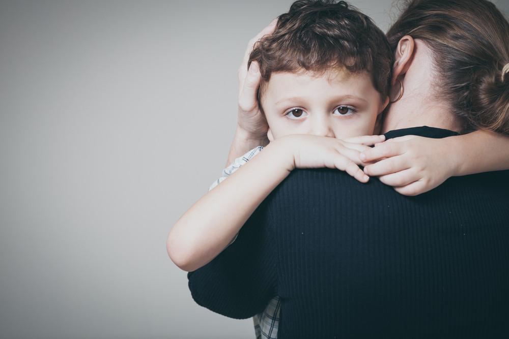 Smutny chłopiec na rękach u mamy