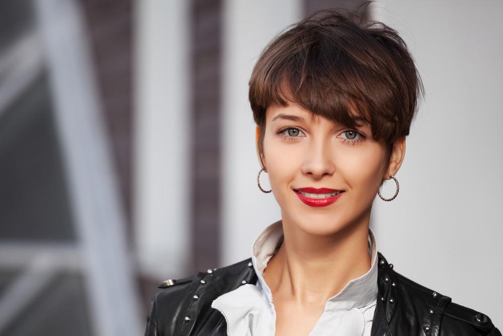 Uśmiechnięta młoda kobieta z krótkimi włosami i czerwonymi ustami